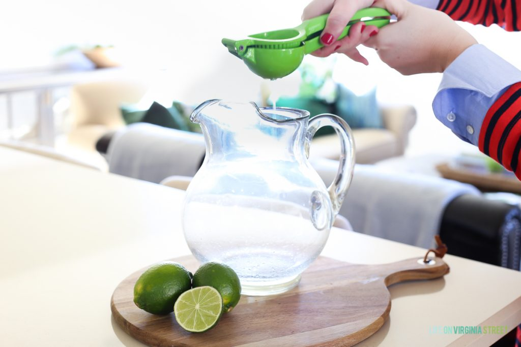 Squeezing lime juice into a clear pitcher.