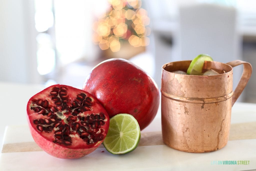 A copper mug and half a pomegranate with a lime beside it on the counter.