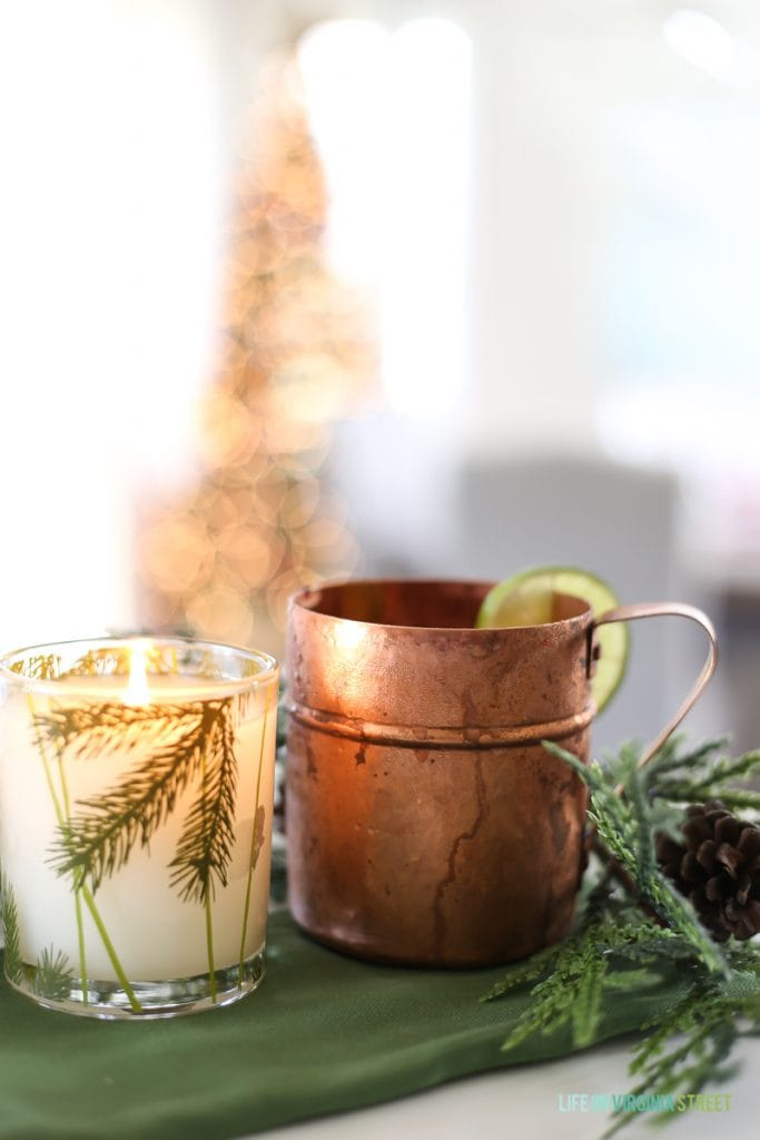 A copper mug and a clear glass with holiday drink inside on a green tablecloth.