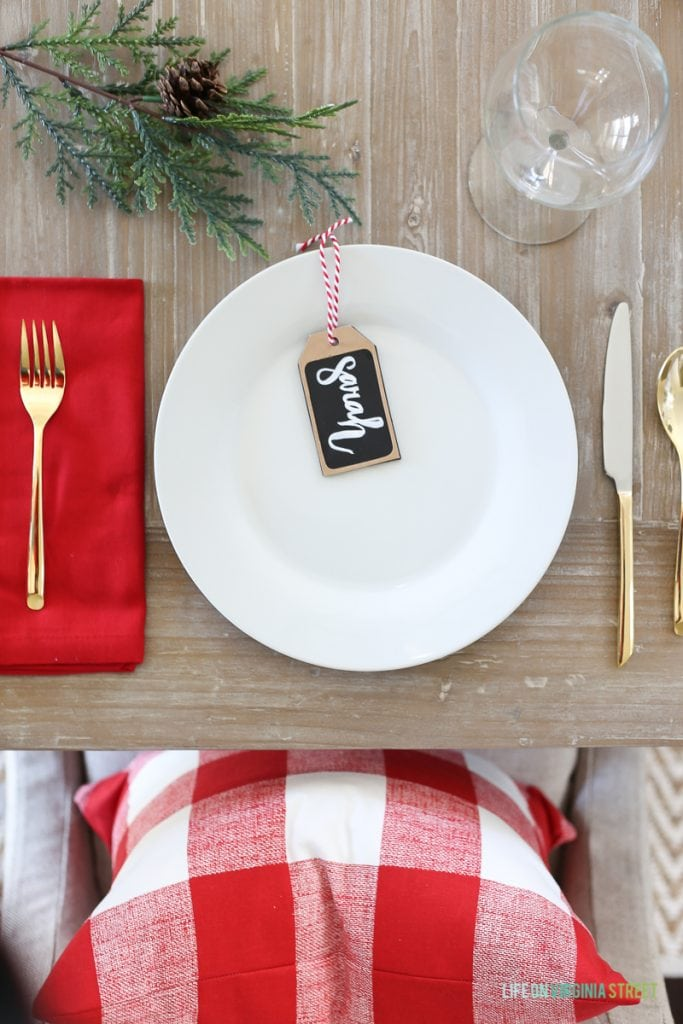 A white plate, red napkin and a tree branch on the decorated table.