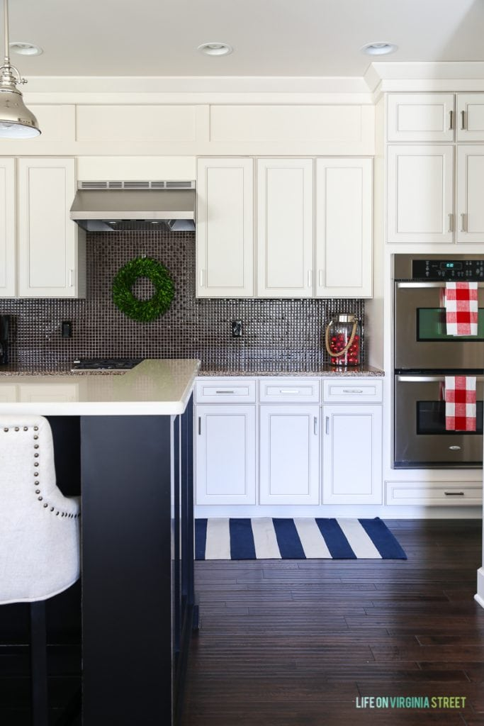 Simple Christmas kitchen with blue and white striped rug, white cabinets, black island, pendant lights, boxwood wreath and red and white buffalo check tea towels.