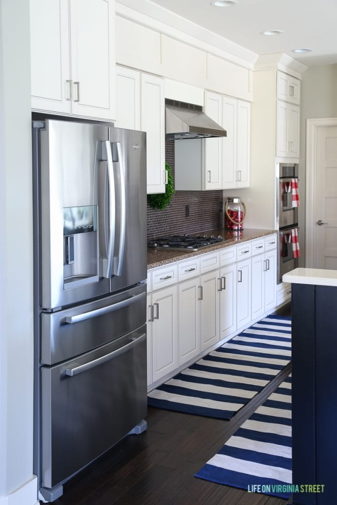 Stainless steel fridge in kitchen with striped blue and white rug on the floor.