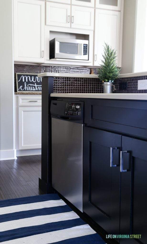 A dark blue kitchen island with a built in dishwasher.