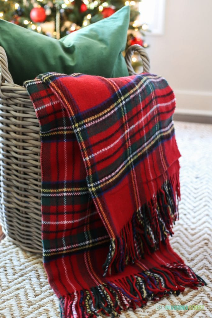 A plaid throw in a basket with a green pillow.