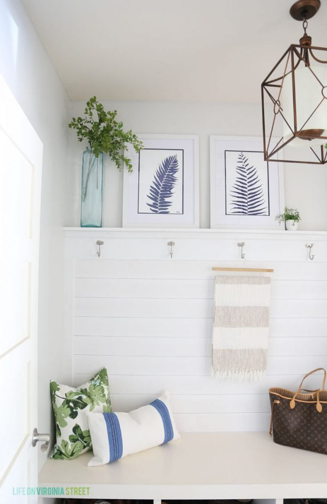 Blue and white mudroom with shiplap walls, striped throw, fig leaf pillows and blue palm artwork!