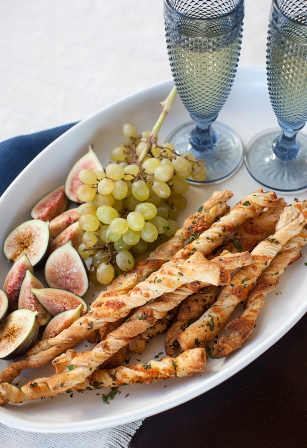 Cheese twists on a plate with grapes and figs.