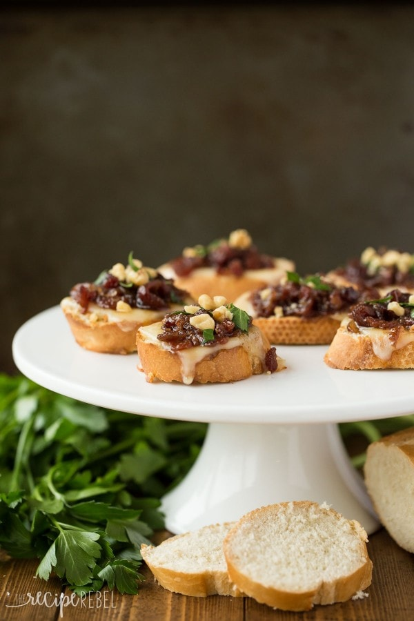 Cranberry bacon crostini's on a white cake stand.