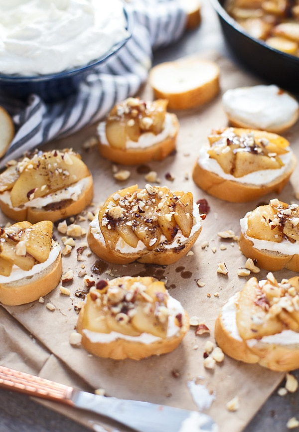 Pear crostini on a wooden tray.