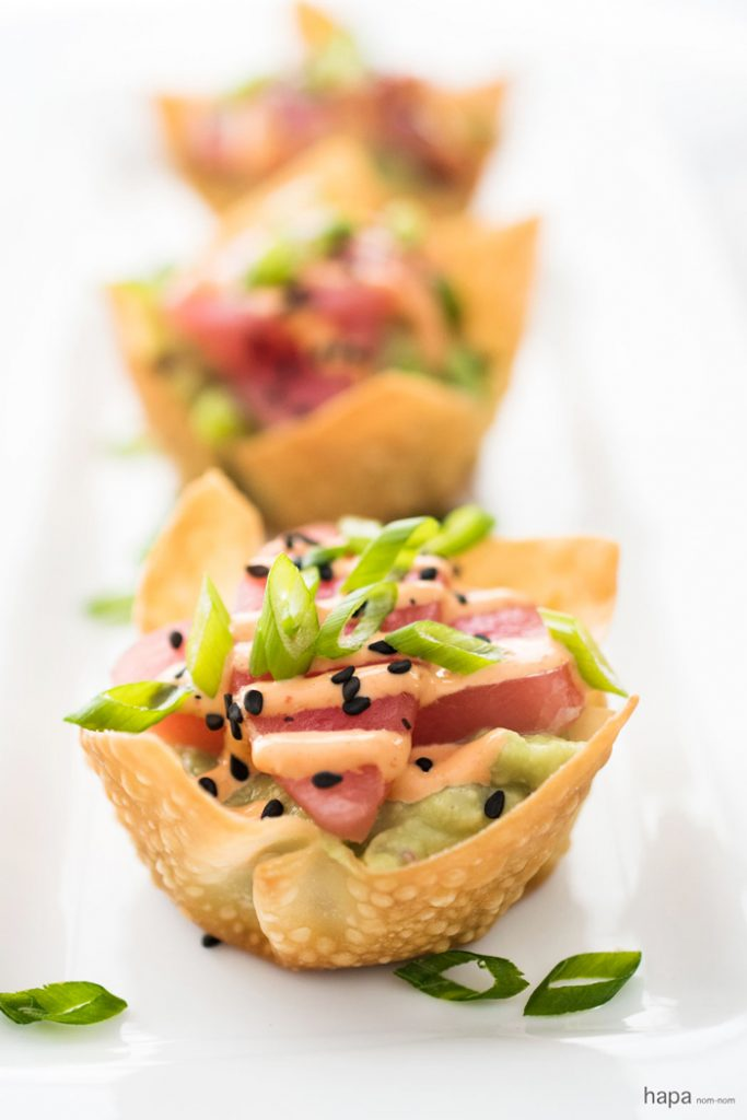 Tuna sashimi in little pastry shells on a white plate.