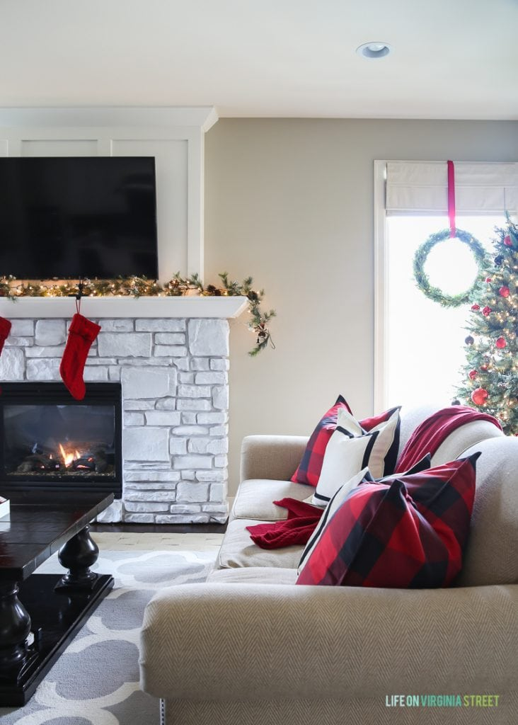 Christmas living room with red and black buffalo check pillows, red stockings and wreaths on the windows.