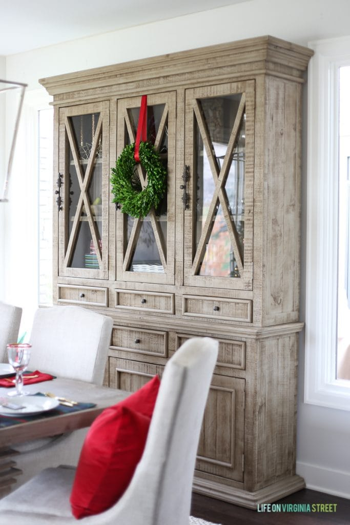 Christmas dining room with boxwood wreath and red ribbon on driftwood hutch.