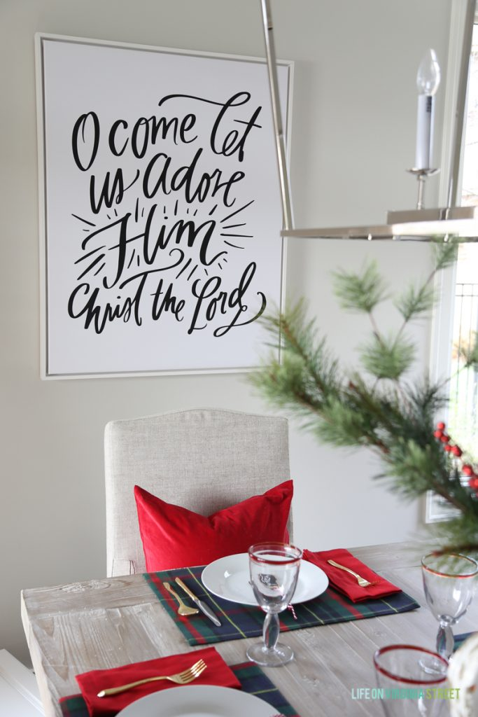 Christmas dining room with navy and red plaid and 'O Come Let Us Adore Him' canvas art.