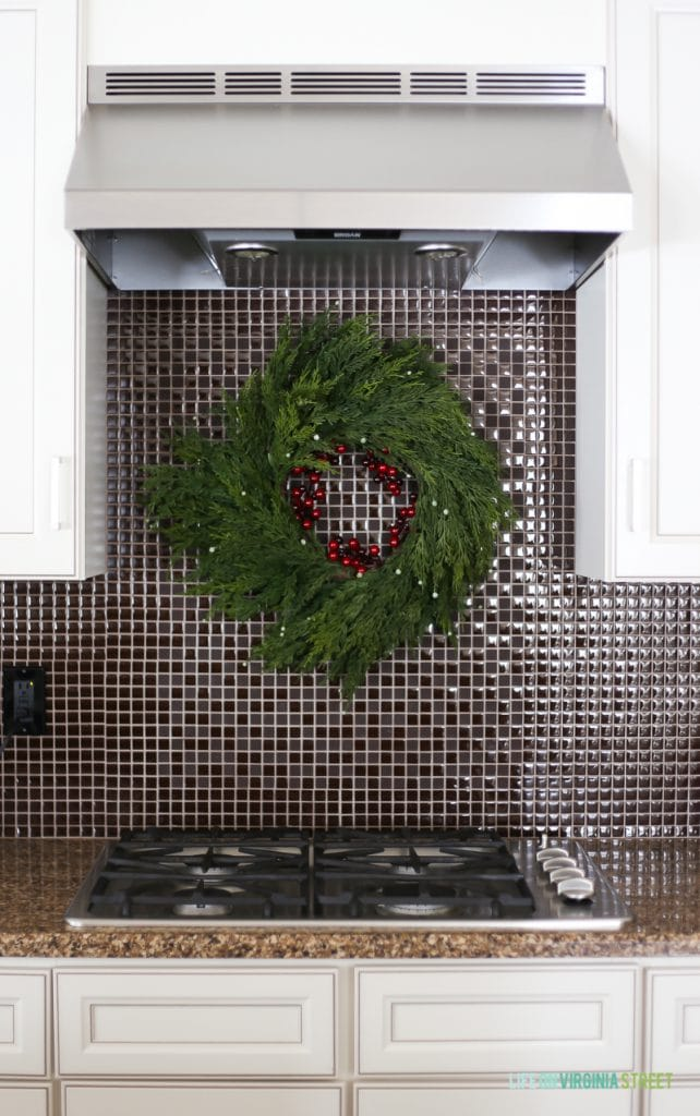 Faux cedar wreath hanging over stove on backsplash in a Christmas kitchen.
