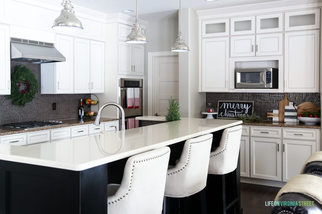 White kitchen with small Christmas tree on counter.
