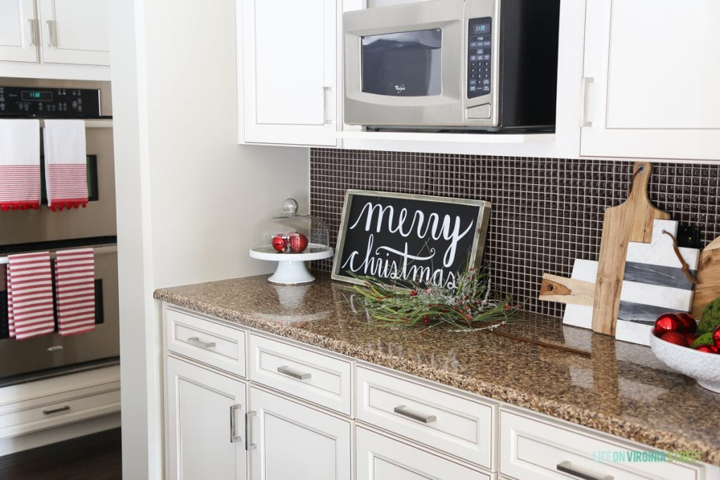 Christmas kitchen with wood Merry Christmas Sign and red and green accents.