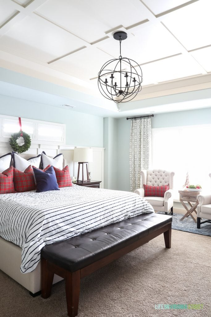 Large bed in middle of room with a chandelier over top of the bed and a bench at the foot of the bed.