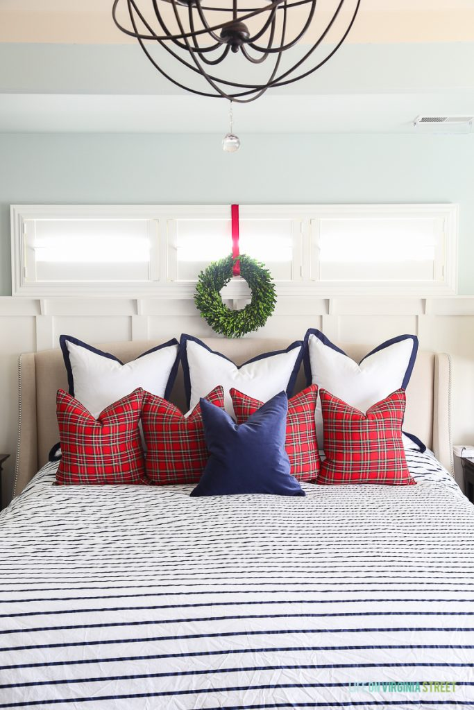 Christmas master bedroom with red plaid pillows, and navy blue and white striped duvet on bed.
