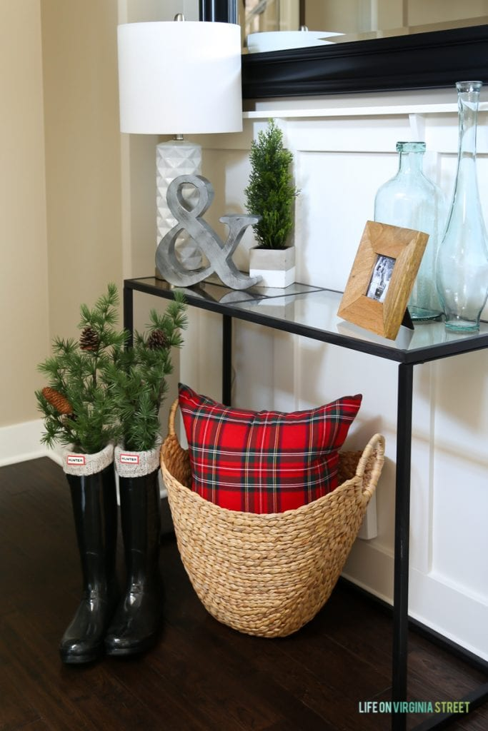 Entryway Christmas vignette with red plaid, basket and Hunter boots.