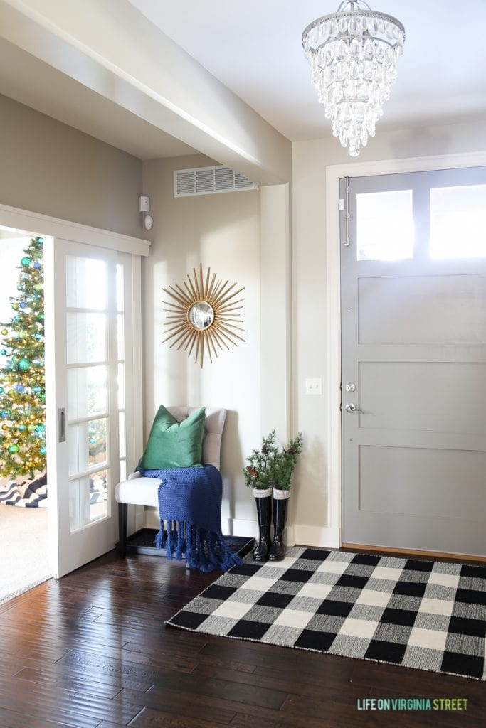 Christmas entryway with gray door, buffalo check rug, chandelier and blue and green accents.