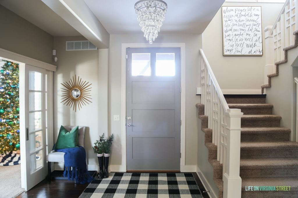 Front door with chandelier in front of it and checked black and white rug on the floor.