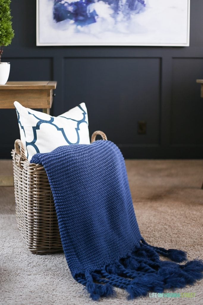 A wicker basket with a navy blue throw and pillow in the basket.
