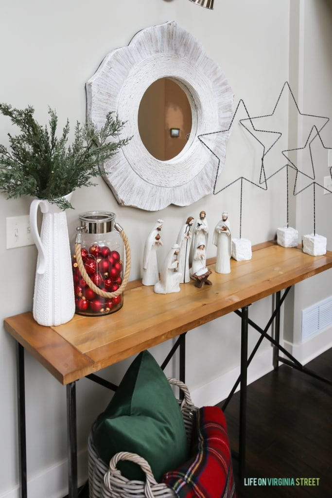 Christmas hallway table with nativity scene, red ornaments in a jar, stars, and a plaid blanket.