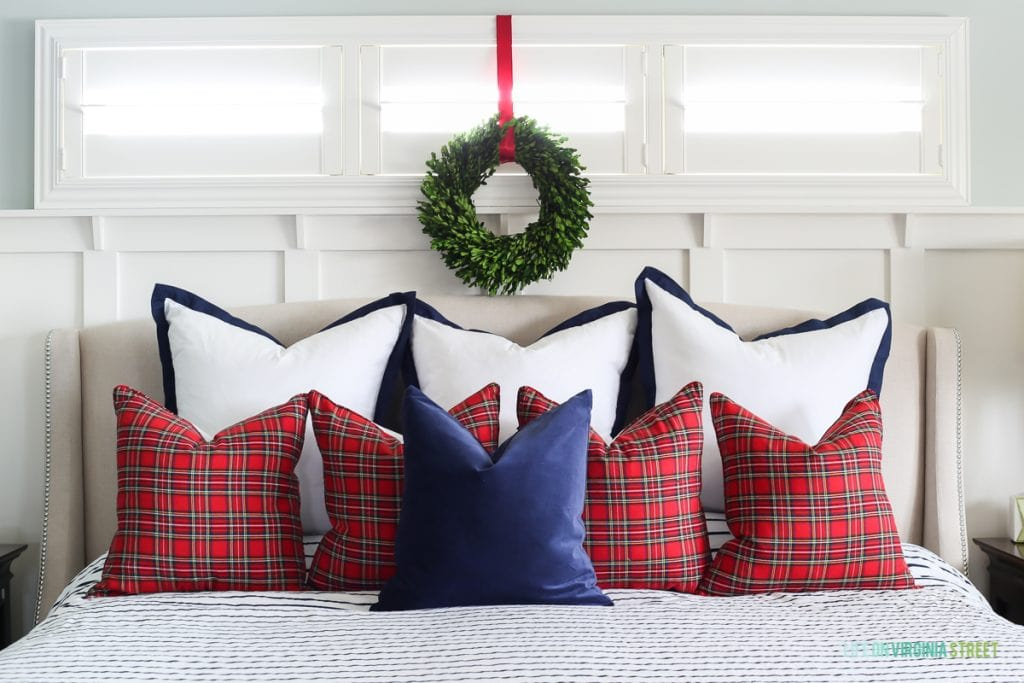 Christmas bedroom with red plaid pillows and navy and white accents. Love the boxwood wreath over the windows!