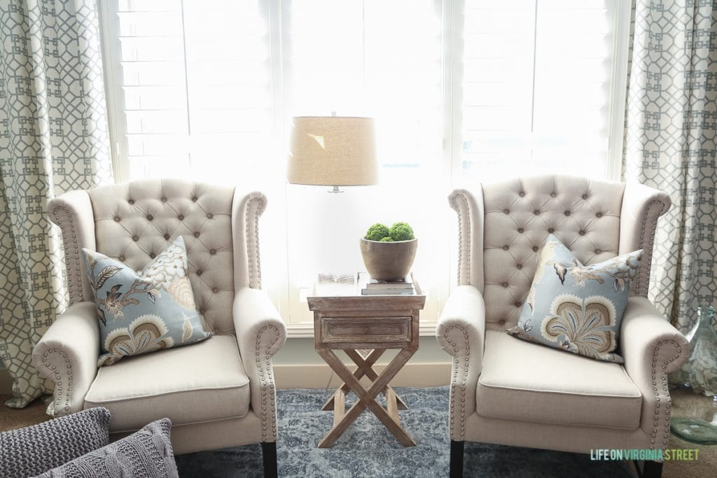 Two neutral colored armchairs in front of window with a side table in between.