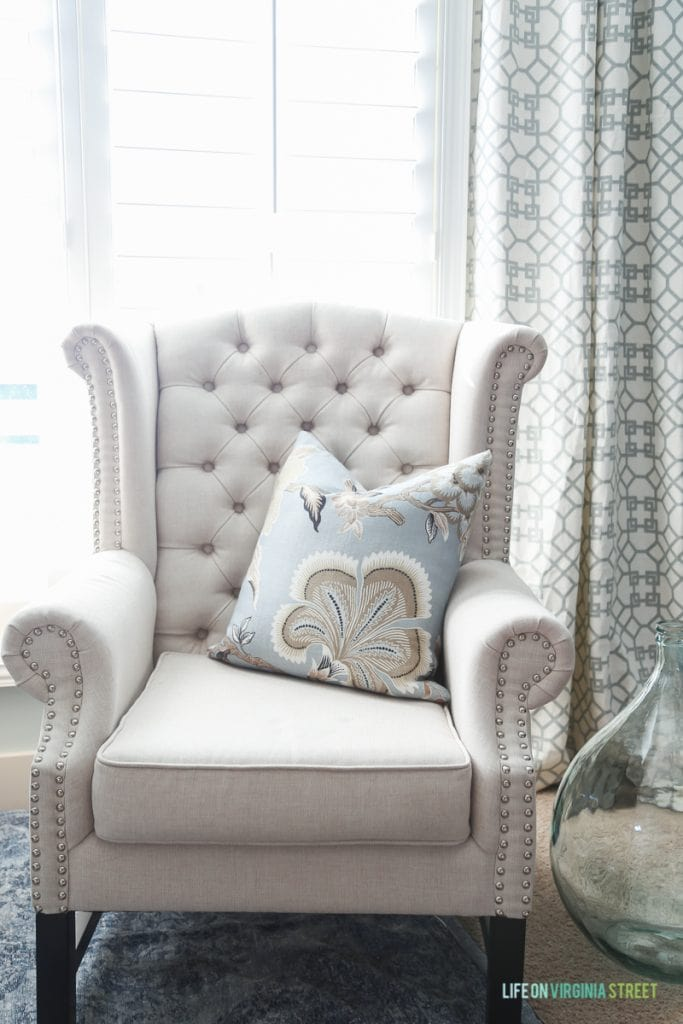 One neutral armchair with light blue, white and beige patterned pillow on the chair.