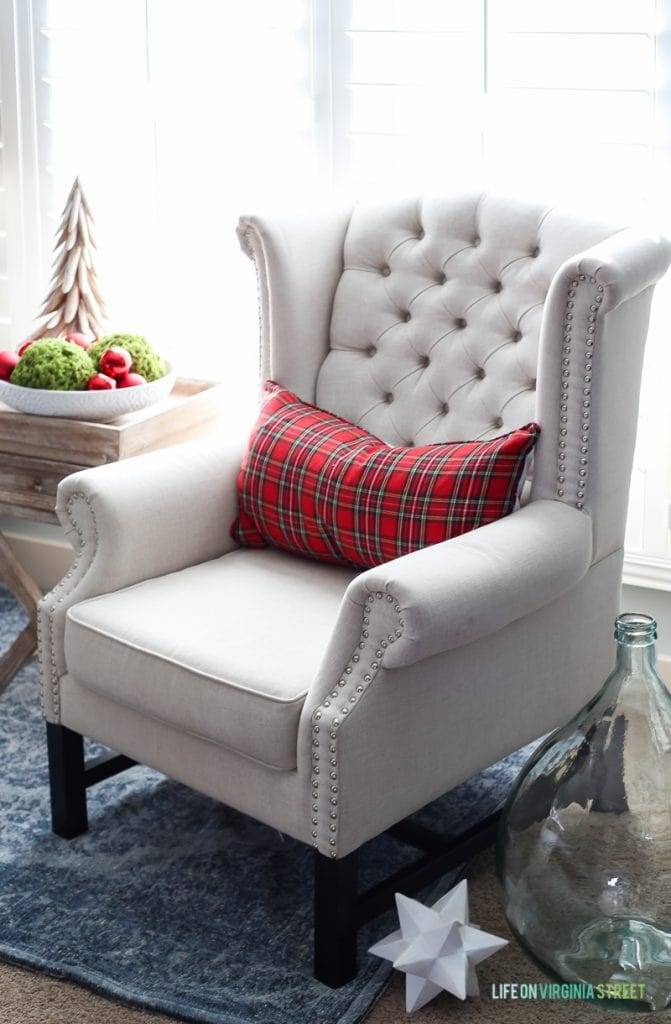 White armchair in bedroom with red plaid pillow on it.