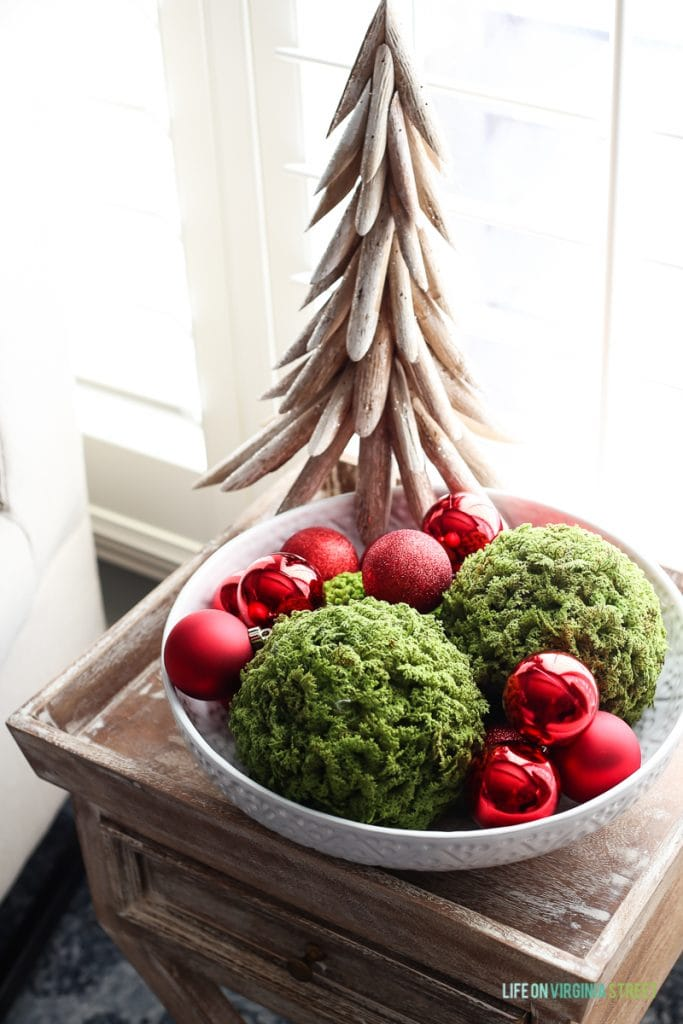A wooden Christmas tree with a decorative bowl filled with moss and ornaments all on the side table in bedroom.