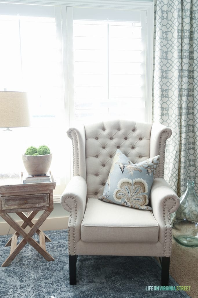 Armchair in corner of room with green and white curtain behind it.