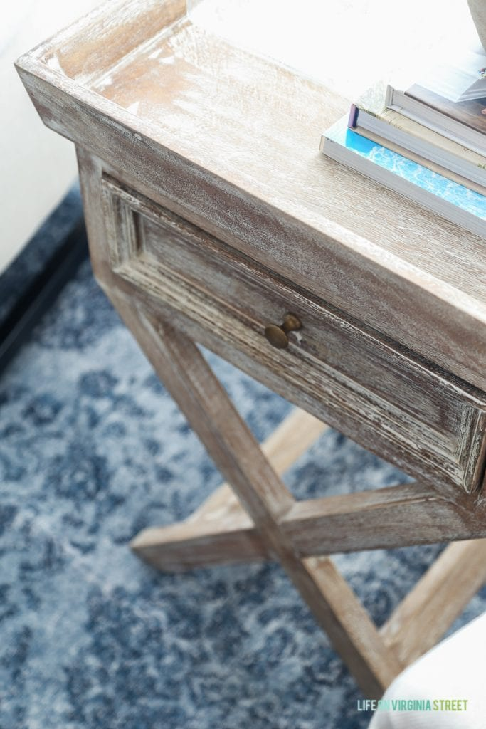Wooden side table with books on it.