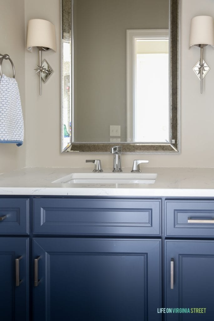 Powder bathroom makeover with freshly painted cabinets and new nautical star sconces, Delta Faucet faucet, Behr Castle Path Walls and Benjamin Moore Hale Navy Cabinets. Love the fresh, nautical vibe! Countertops are Daltile One Quartz in the Luminesce color.