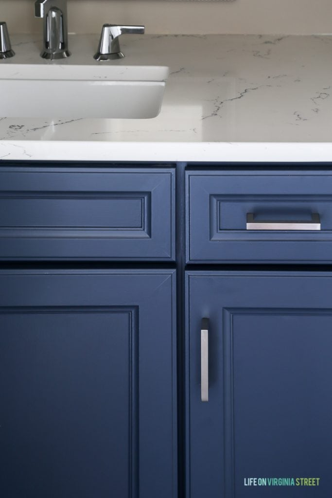 Powder bathroom cabinets freshly painted in a cool navy blue, Delta Faucet faucet, Behr Castle Path Walls and Benjamin Moore Hale Navy Cabinets. Love the fresh, nautical vibe! Countertops are Daltile One Quartz in the Luminesce color.