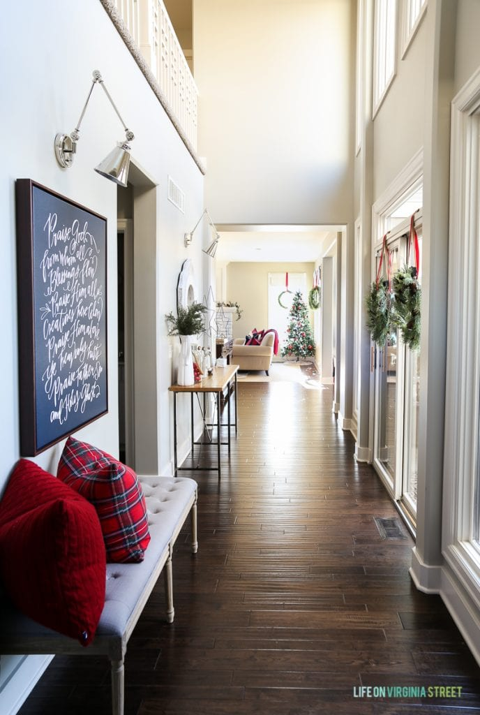 Christmas entryway hallway with linen bench, red plaid pillows, wreaths, swing-arm sconces and 'Doxology' canvas artwork.