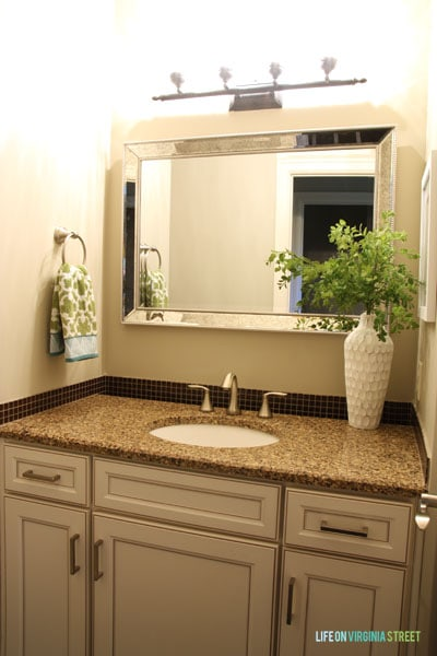 I tried to refresh the powder bathroom with a new silver-framed mirror, but that didn't do much to lighten the space. More updates were needed.
