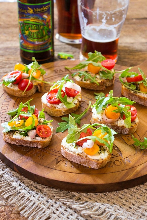 Little toasts with tomatoes and arugula on a wooden tray.