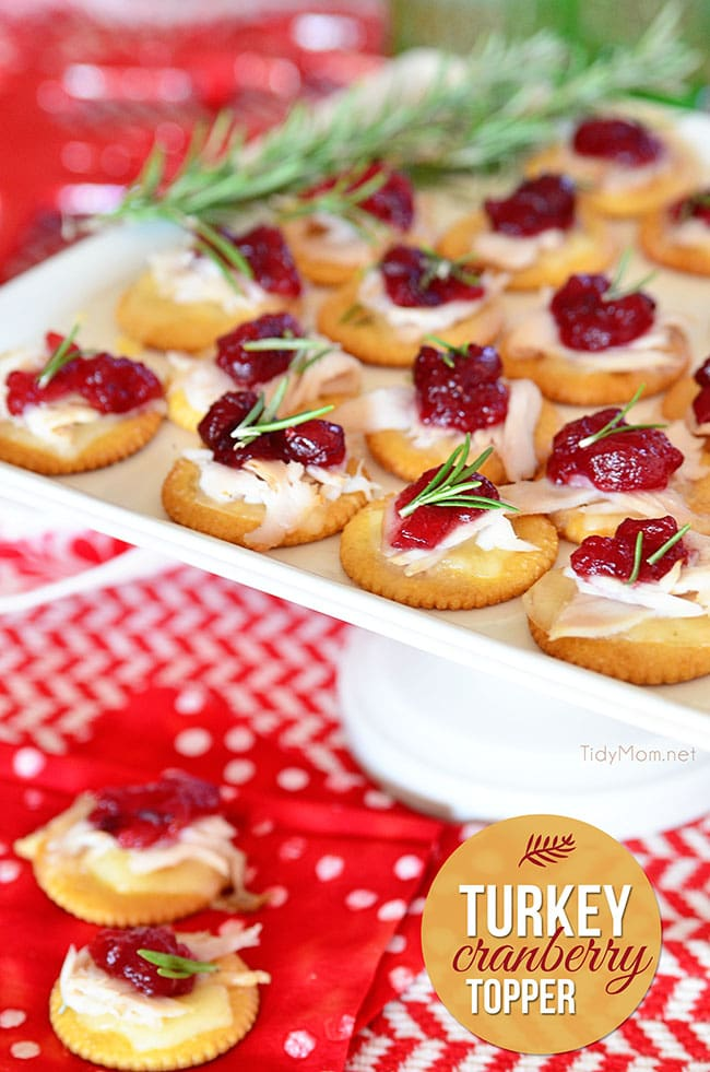 Crackers with turkey and cranberry on a white tray.