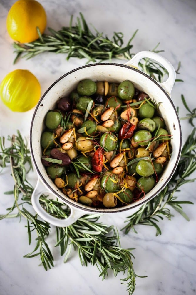 Marinated olives in a white pot with rosemary around it and lemons.