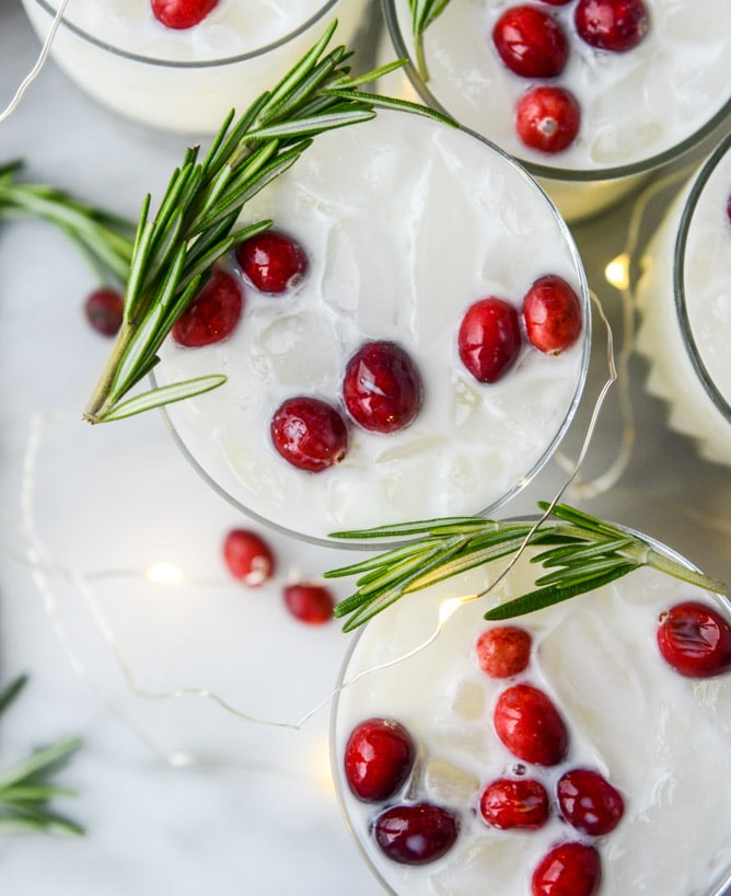 White Christmas Margarita Punch - So festive with red cranberries and green rosemary to compliment this white drink. Perfect look for Christmas!