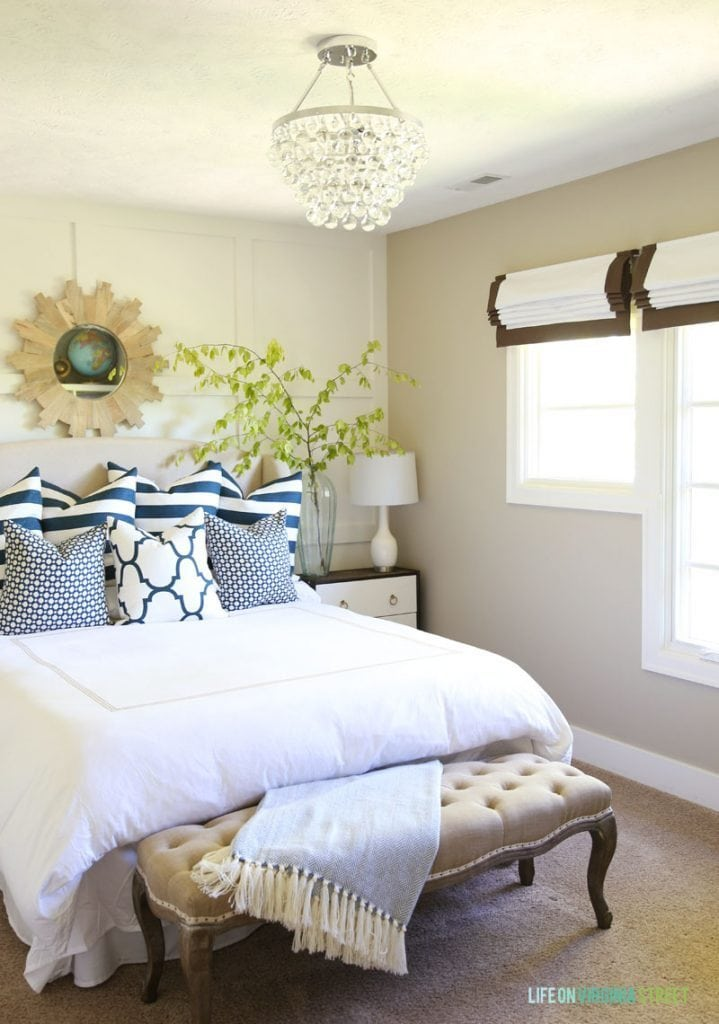 Guest bedroom with white bedding, crystal chandelier, navy striped pillows and roman shades. Love the board and batten feature wall behind the bed!