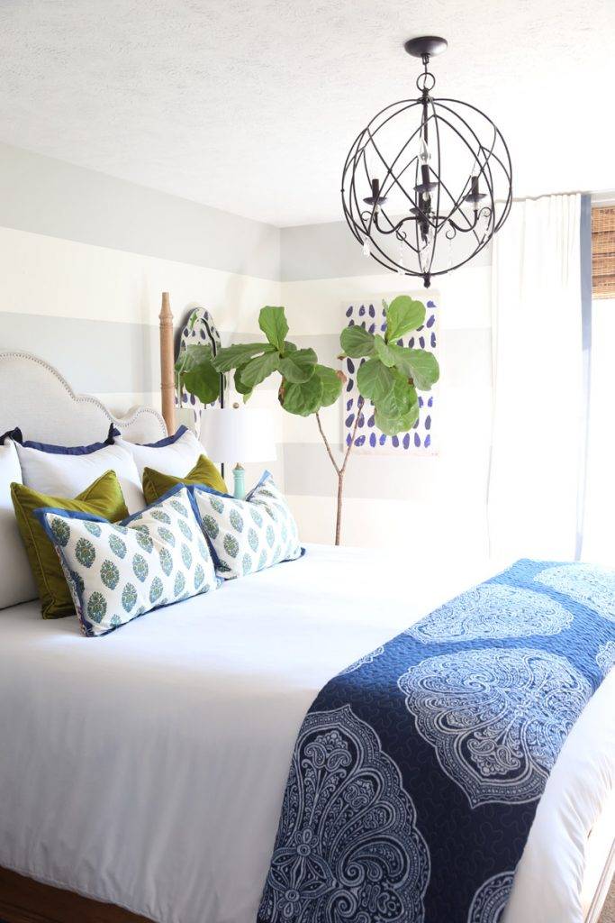 Bedroom with striped walls, blue and green bedding and orb chandelier.