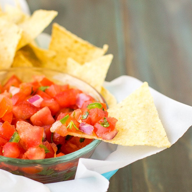 Tomato salsa in a bowl with corn chips.