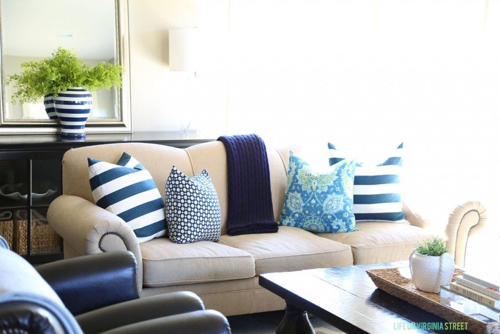 Spring living room with navy blue striped pillows and aqua suzani pillows.