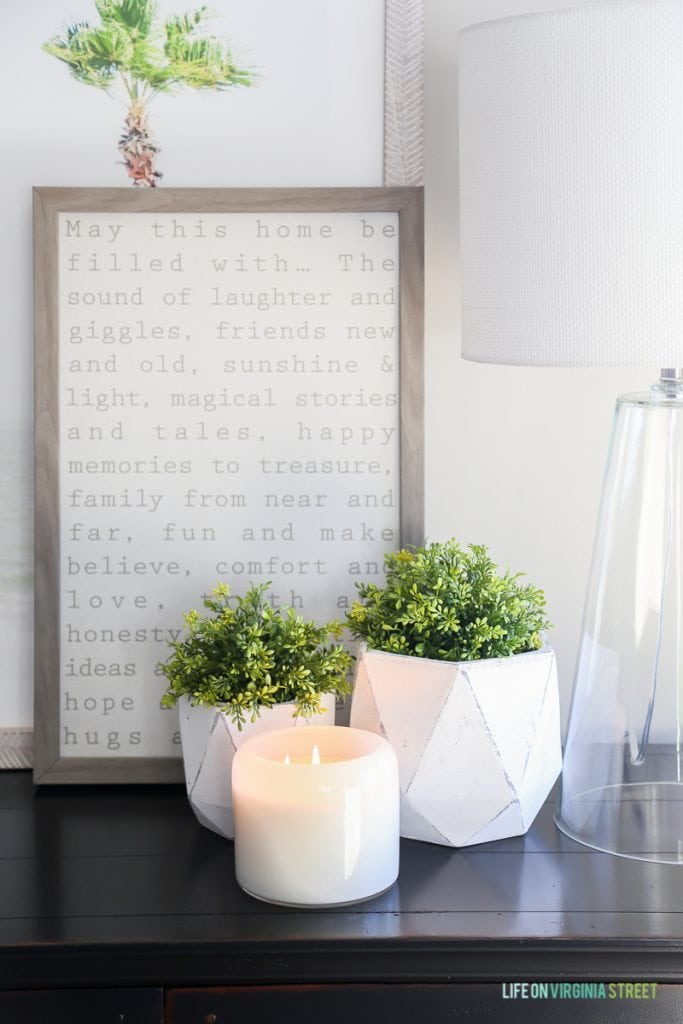 A lit candle on a wooden table with plants around it and a graphic word framed picture behind it.