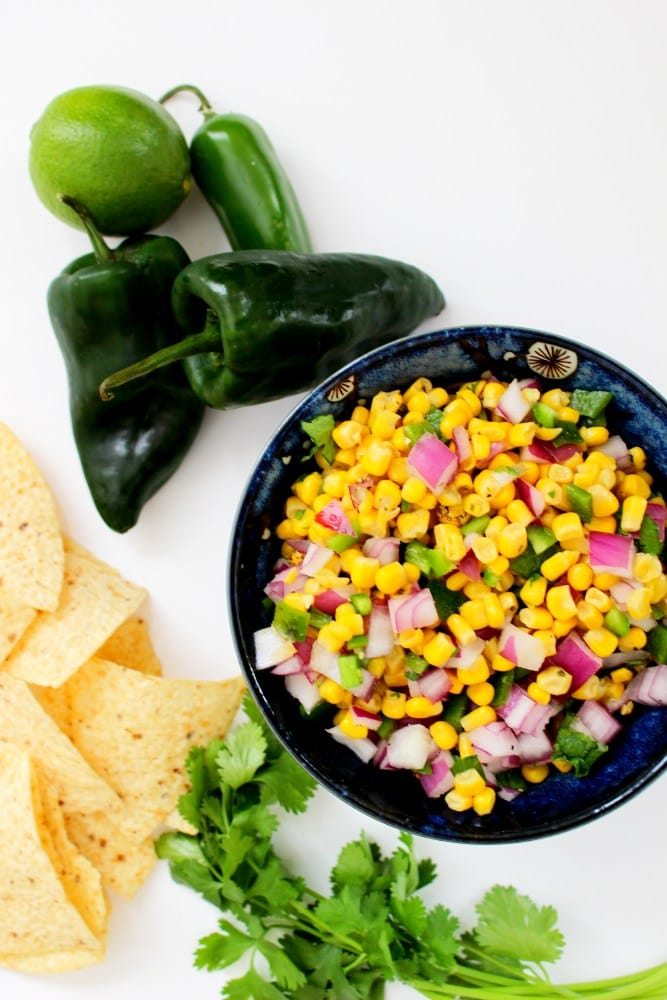 Corn salsa in a bowl with peppers beside it.