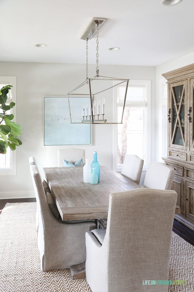 Coastal dining room with natural wood table, linen chairs, fiddle leaf fig tree, Darlana linear pendant and blue ocean art. Love our new dining room Roman shades!