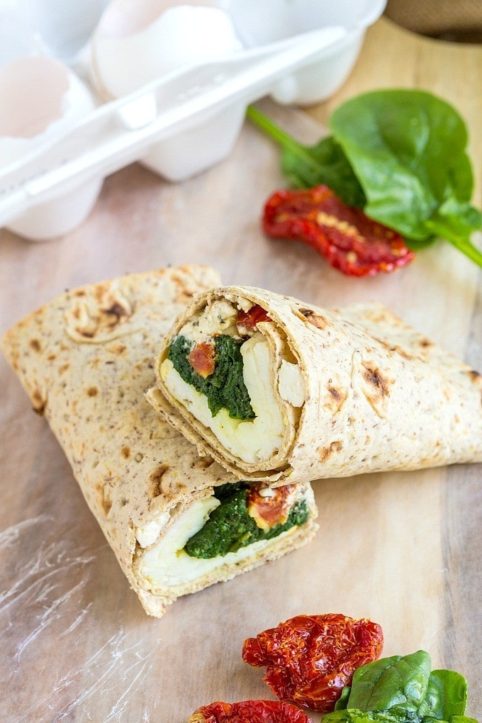 A spinach and feta breakfast wrap on the counter with spinach leaves beside it.