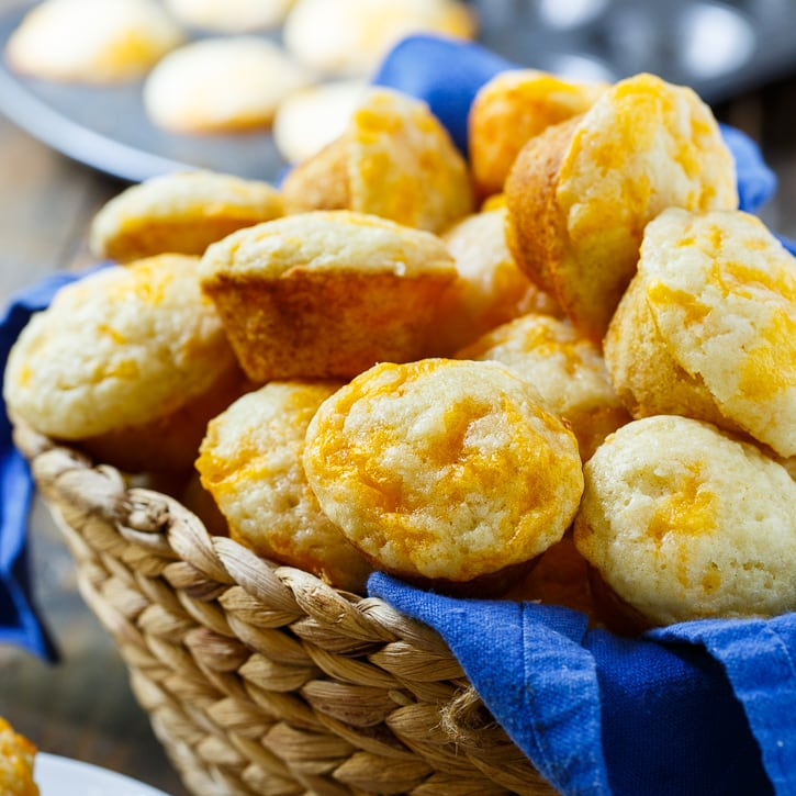 Cheesy biscuits in a basket with a blue cloth.